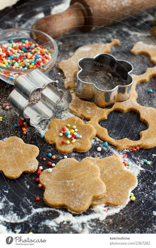 Kochen von Keksen mit Blumenkeksausstechern auf einem dunklen Tisch Teigwaren Backwaren Dessert Küche Metall machen braun Tradition backen Bäckerei Biskuit