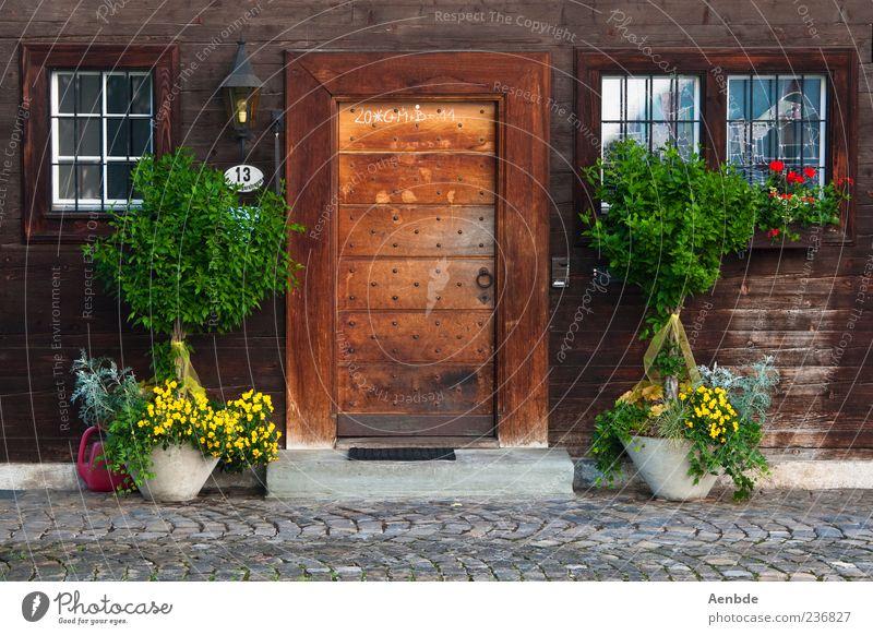 Bauernhaus Dorf Haus Hütte Mauer Wand Fassade Tür Fußmatte braun Holz Holzhaus Sträucher Eingang rustikal gepflegt Idylle Farbfoto mehrfarbig Außenaufnahme