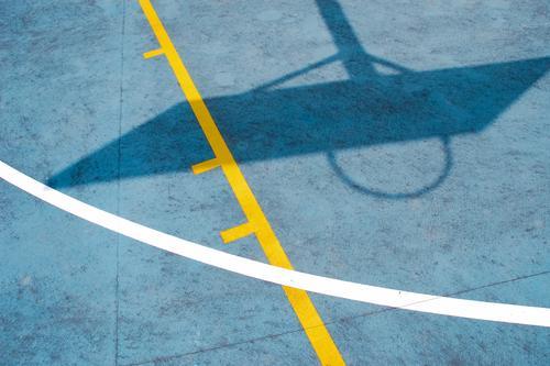 Schattenwurf auf Basketballfeld Basketballkorb Basketballplatz Australien Kunststoff Linie eckig unten Wärme blau gelb Stimmung Kraft Tatkraft Wachsamkeit