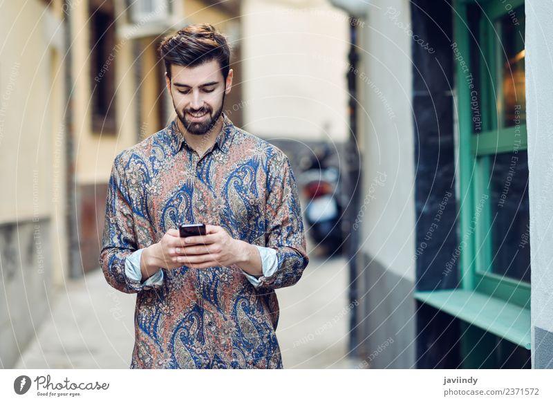 Junger lächelnder Mann schaut auf sein Smartphone im Freien. Lifestyle Stil schön Haare & Frisuren Telefon PDA Mensch Junger Mann Jugendliche Erwachsene 1
