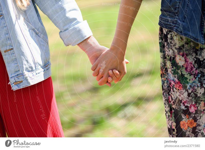 Zwei junge Frauen beim Gehen, die ihre Hände halten. Lifestyle Freude Glück schön Mensch Junge Frau Jugendliche Erwachsene Freundschaft Paar Hand 2 18-30 Jahre