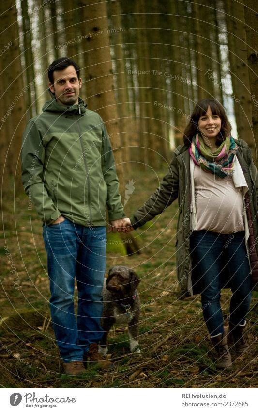 Paar geht im Wald spazieren Blick nach vorn Ganzkörperaufnahme Totale Schwache Tiefenschärfe Unschärfe Schatten Tag Außenaufnahme Farbfoto Spaziergang Babybauch