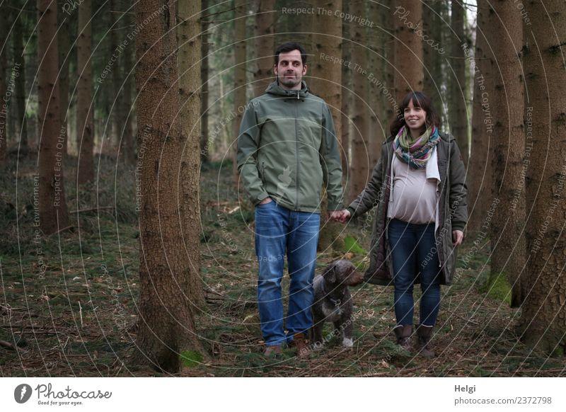 junges Paar mit Hund steht im Wald, die Frau ist schwanger Mensch maskulin feminin Erwachsene Mann Partner 2 30-45 Jahre Umwelt Natur Landschaft Frühling Baum