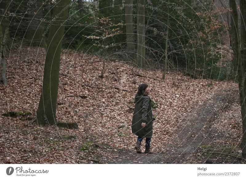 Gesundheit   Junge Frau geht im Herbstwald spazieren und  schaut lachend zur Seite weiblich brünett langhaarig Bekleidung Mantel Stiefel Wald Waldspaziergang