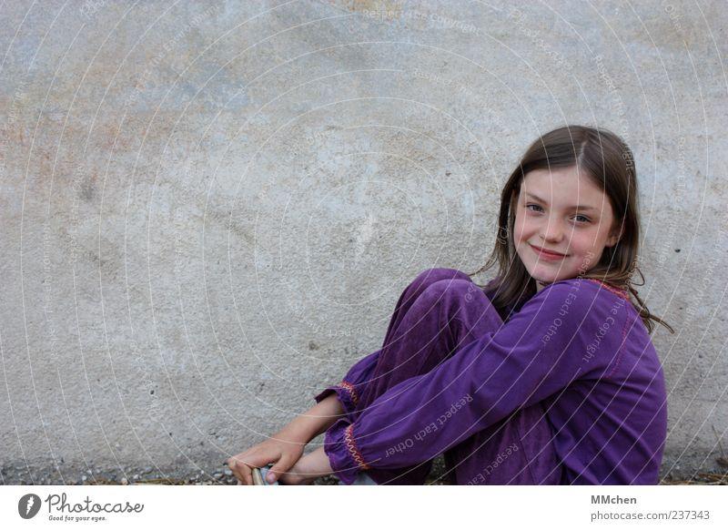 Ich kann in 3 Sekunden die Welt erobern Kind Mädchen Kindheit 1 Mensch 8-13 Jahre Mauer Wand langhaarig Scheitel Blick sitzen grau violett Glück Fröhlichkeit