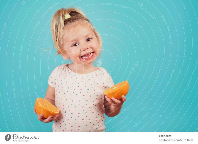 lächelndes Baby mit einer Orange auf blauem Hintergrund Lebensmittel Frucht Ernährung Essen Lifestyle Freude Mensch feminin Mädchen Kindheit 1 3-8 Jahre Fressen