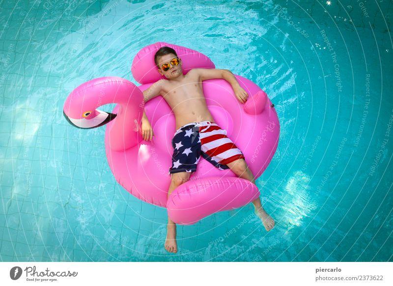 Kleiner Junge auf einem aufblasbaren Flamingo in einem Schwimmbad. Lifestyle Freude Erholung Freizeit & Hobby Ferien & Urlaub & Reisen Sommer Sonne Sonnenbad