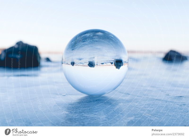 Glaskugel, die auf Eis auf einem gefrorenen See balanciert. Design schön Wellness Meditation Winter Schnee Berge u. Gebirge Dekoration & Verzierung Natur