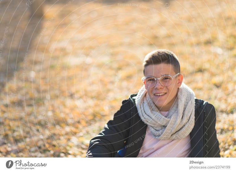 Stylisch lächelnder Teenager auf dem Boden in einem Stadtpark. Lifestyle Freude Glück Schulkind Studium PDA Mensch maskulin Junge Junger Mann Jugendliche