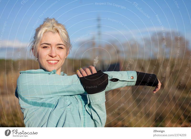 Eine schöne junge blonde Frau, die sich in einem Park ausstreckt. Lifestyle Glück Körper Sport Leichtathletik Sportler Joggen Mensch feminin Junge Frau
