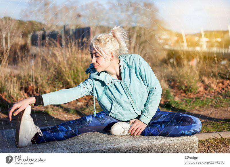 blonde Frau, die im Gras sitzt und sich in einem Park ausstreckt. Lifestyle Glück schön Körper Freizeit & Hobby Sport Leichtathletik Sportler Joggen Mensch