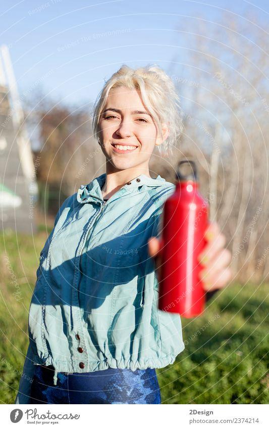Läuferin, die im Freien steht und eine Trinkflasche hält. trinken Flasche Lifestyle Glück schön Wellness Erholung Sommer Sport Joggen Mensch feminin Junge Frau