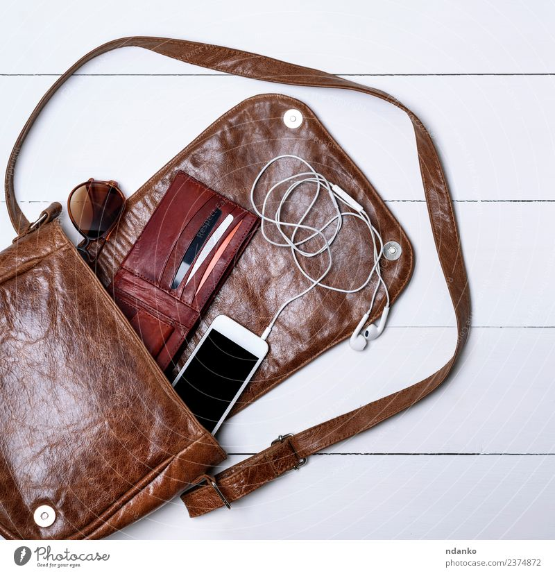 offene weibliche braune Ledertasche elegant Stil Design PDA Bildschirm Mode Accessoire Sonnenbrille modern schwarz weiß Farbe Brille Kopfhörer Gerät Schnur