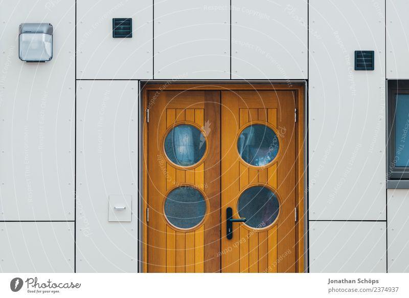 Tür mit runden Fenstern an weißer Fassade Holztür Haustür Außentür runde fenster Guckloch braun modern Hafen maritim minimalistisch geometrisch Architektur haus