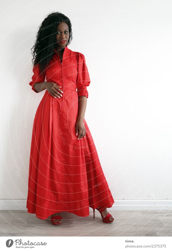 Apolline Raum feminin Frau Erwachsene 1 Mensch Kleid Damenschuhe brünett langhaarig Locken beobachten Lächeln Blick stehen warten schön rot selbstbewußt