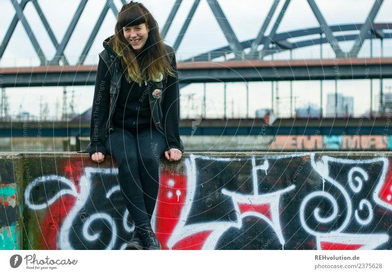 Junge Frau sitzt auf einer Mauer Blick in die Kamera Ganzkörperaufnahme Porträt Schwache Tiefenschärfe Unschärfe Tag Außenaufnahme Farbfoto rebellisch natürlich