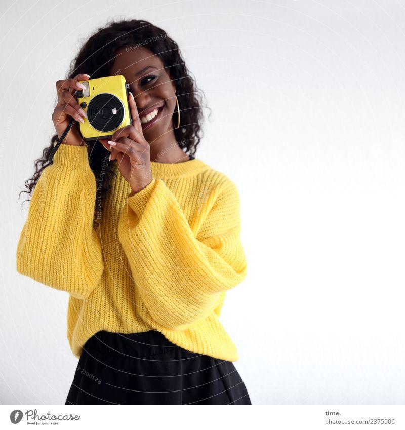 Apolline feminin Frau Erwachsene 1 Mensch Rock Pullover Ohrringe schwarzhaarig langhaarig Locken Fotokamera beobachten Lächeln lachen Blick stehen schön gelb