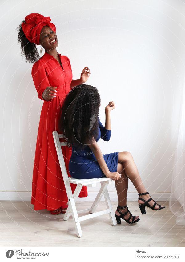 Apolline und Arabella Stuhl Raum feminin Frau Erwachsene 2 Mensch Kleid Damenschuhe Kopftuch schwarzhaarig langhaarig Locken lachen sitzen stehen Fröhlichkeit