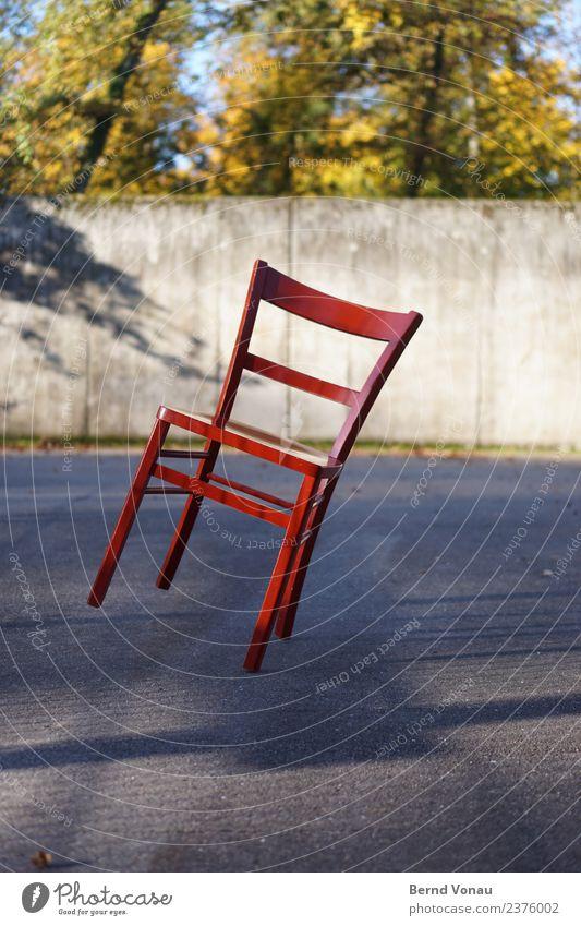 Roter Holz-Stuhl in Schräglage auf sonnigem Asphalt hell mehrfarbig Neigung Gleichgewicht unsicher vierbeinig Vierbeiner klassisch Beton lackiert hotchair