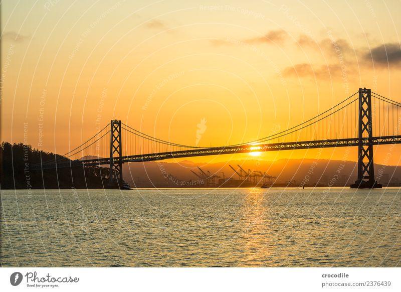 # 751 Oakland Bay Bridge San Francisco Hafen Meer Sonnenaufgang Anlegestelle Brücke ruhig Gegenlicht Farbfoto orange Licht Hängebrücke Einsamkeit Kran