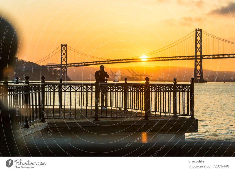 # 750 Oakland Bay Bridge San Francisco Hafen Meer Sonnenaufgang Anlegestelle Mann Fotograf Brücke ruhig Gegenlicht Farbfoto orange Licht Hängebrücke Einsamkeit