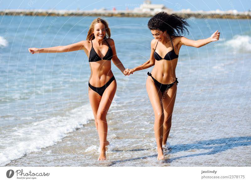Zwei junge Frauen im Bikini an einem tropischen Strand. Lifestyle Freude Glück schön Körper Haare & Frisuren Freizeit & Hobby Ferien & Urlaub & Reisen Tourismus
