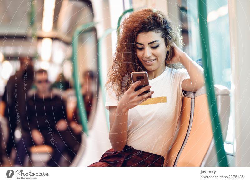 Eine Frau in der U-Bahn schaut auf ihr Smartphone. Lifestyle Glück schön Haare & Frisuren Ferien & Urlaub & Reisen Tourismus Ausflug Telefon PDA Mensch