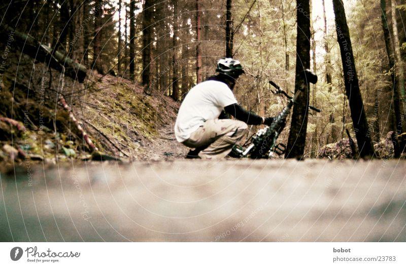 Ein Biker hockt im Walde ganz still und stumm ... Blatt Sport Holz Fahrrad Verkehr Feder Helm Ausdauer Baumrinde hocken Gelände Mountainbike transpirieren