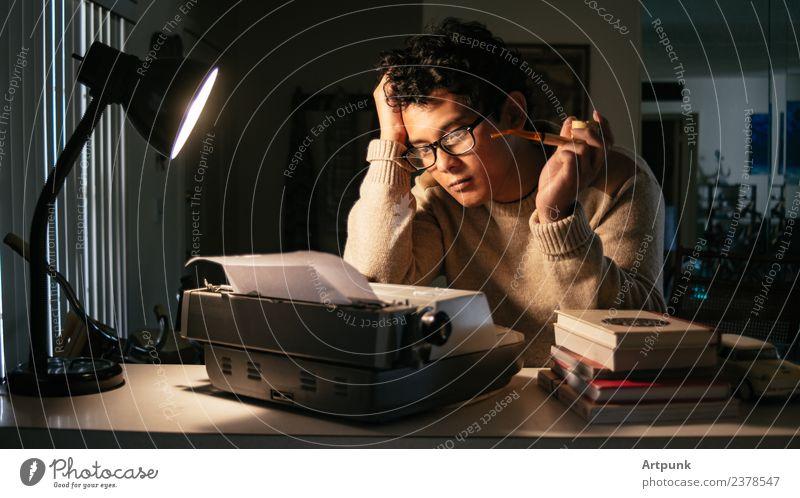Ein junger Mann sitzt vor einer Schreibmaschine. 18-30 Jahre Junger Mann Asiate Schriftsteller Lampe Arbeit & Erwerbstätigkeit Literatur Pfeife Rauchen Buch