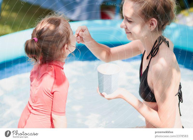 Teenager Mädchen mit ihrer kleinen Schwester genießen es, Eis zu essen. Dessert Speiseeis Essen Lifestyle Freude Glück schön Schwimmbad Freizeit & Hobby