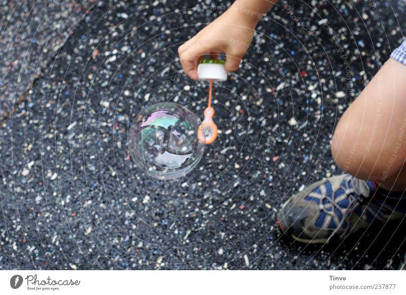 Save The World Kind Hand schwarz Spielen Beine Schuhe rund zart fangen Straßenbelag Blase Seifenblase Turnschuh hocken Kinderspiel bücken