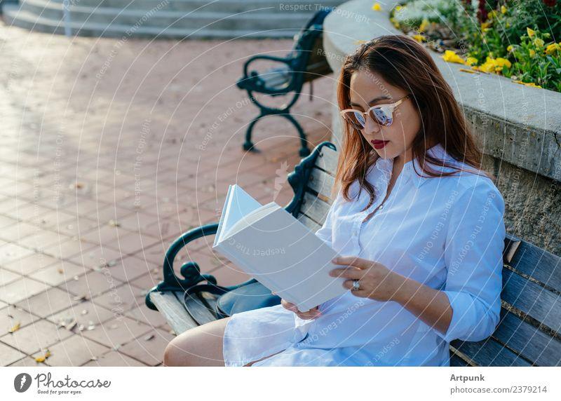 Junge asiatische Frau beim Lesen eines Buches bibliophil lesen weiß Hemd Bank Park Bildung Schule Literatur sitzen Sonnenbrille Wort Bucheinband Erholung