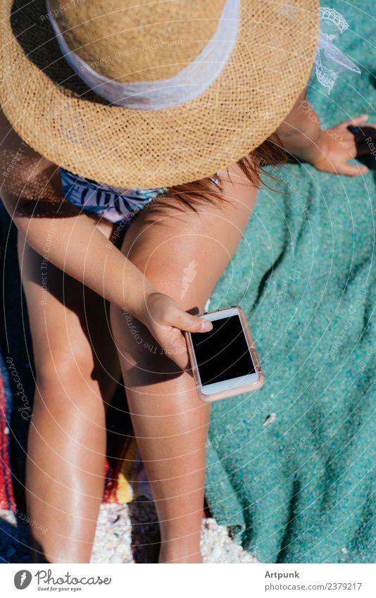 Eine junge Frau, die am Strand schreibt. Jugendliche 18-30 Jahre Junge Frau Beine Hut Decke Handtuch PDA Technik & Technologie Außenaufnahme WiFi Daten Bikini