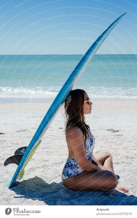 Eine junge Frau sitzt unter einem Surfbrett. 18-30 Jahre Lateinamerikaner Südamerika Asiate Sommer Strand Sand Sonne Meer Wasser Bikini langhaarig