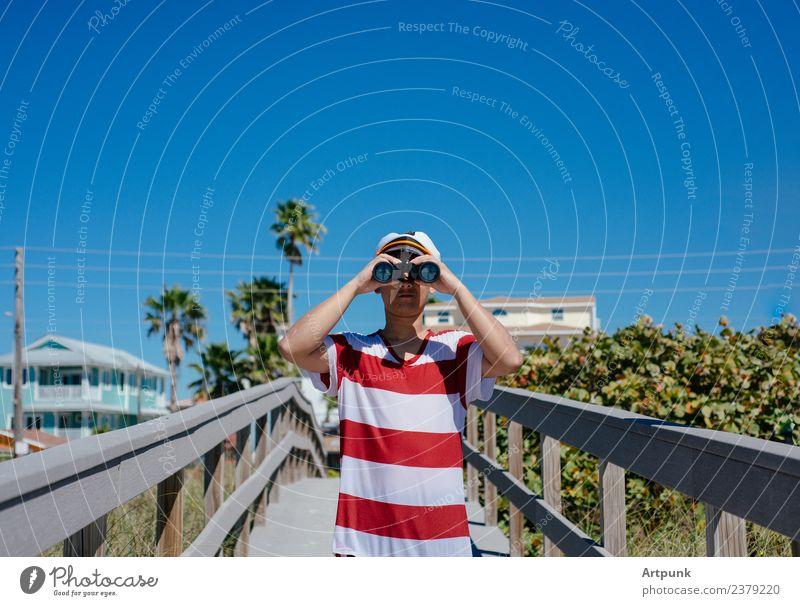 Ein junger Seemann, der durch ein Fernglas schaut. Matrosen Sommer Strand Ferien & Urlaub & Reisen Hut Kapitän Palme tropisch Anlegestelle Pflanze Sand Baum
