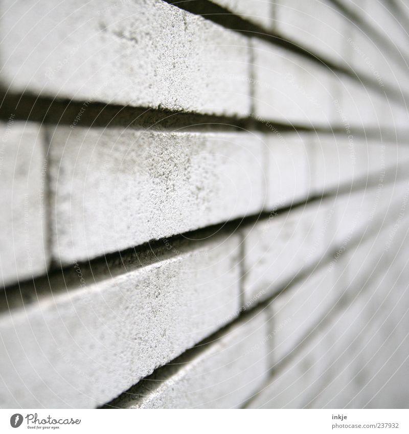 immer an der Wand lang kalt grau Stein Mauer Linie Fassade Beton Streifen Backstein Sandstein Backsteinwand Fluchtpunkt Steinwand