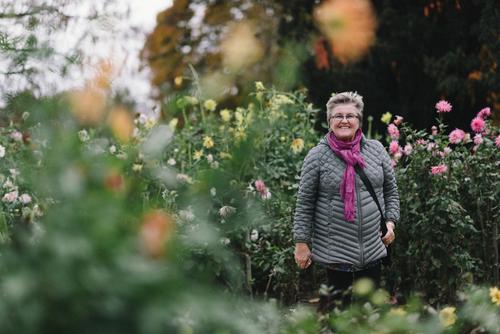 Fröhliche Rentnerin Mensch Frau Erwachsene Weiblicher Senior 1 45-60 Jahre 60 und älter Herbst Dahlien Garten Park Lächeln lachen Ferien & Urlaub & Reisen