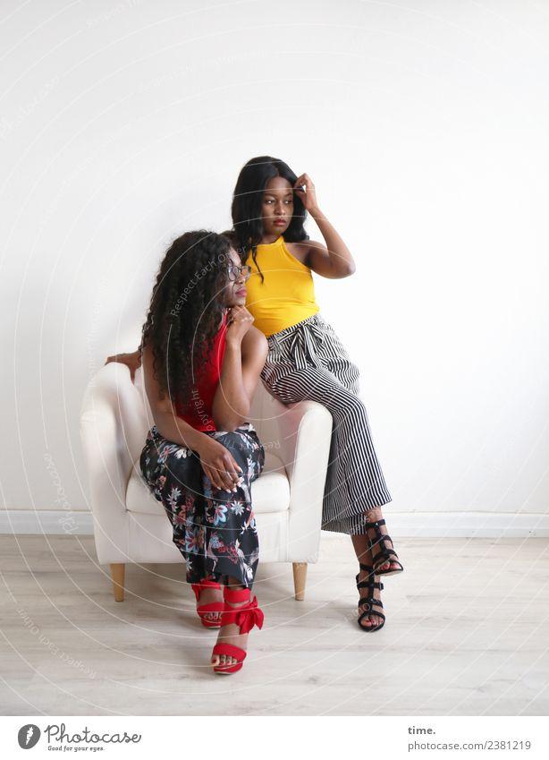 Apolline und Arabella Sessel Raum feminin Frau Erwachsene 2 Mensch T-Shirt Hose Brille Damenschuhe schwarzhaarig brünett langhaarig Afro-Look beobachten