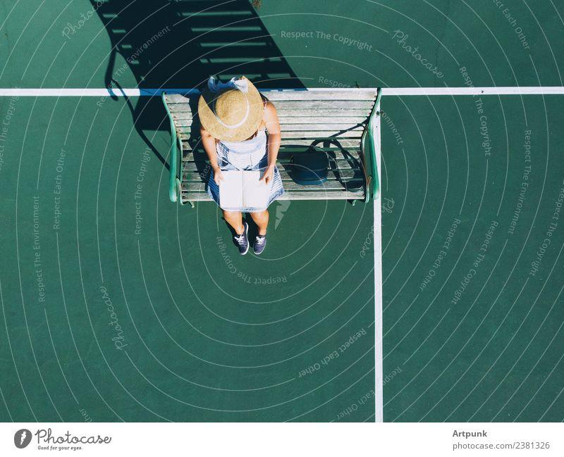 Eine Luftaufnahme der jungen Frau, die ein Buch liest. Fluggerät Tasche lesen Leser Hut Bank Schatten Dröhnen Tennisplatz Außenaufnahme Sonnenuntergang Sommer