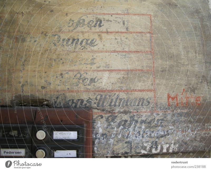Zeitreise Gebäude Mauer Wand Namensschild Klingel Stein Holz Metall Schriftzeichen alt dreckig authentisch braun rot schwarz weiß Verfall Farbfoto Außenaufnahme