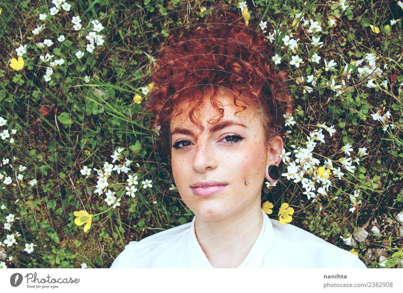 Junge rothaarige Frau, die sich über ein Blumenfeld legt. Lifestyle Stil schön Haare & Frisuren Haut Gesicht Sommersprossen Sinnesorgane Erholung Duft Mensch