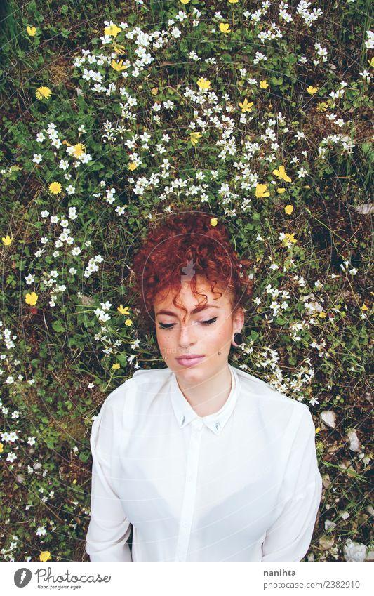 Junge Frau, die sich auf einem Blumenfeld ausruht. Lifestyle Stil Freude schön Haare & Frisuren Gesundheit Wellness harmonisch Sinnesorgane Erholung Mensch