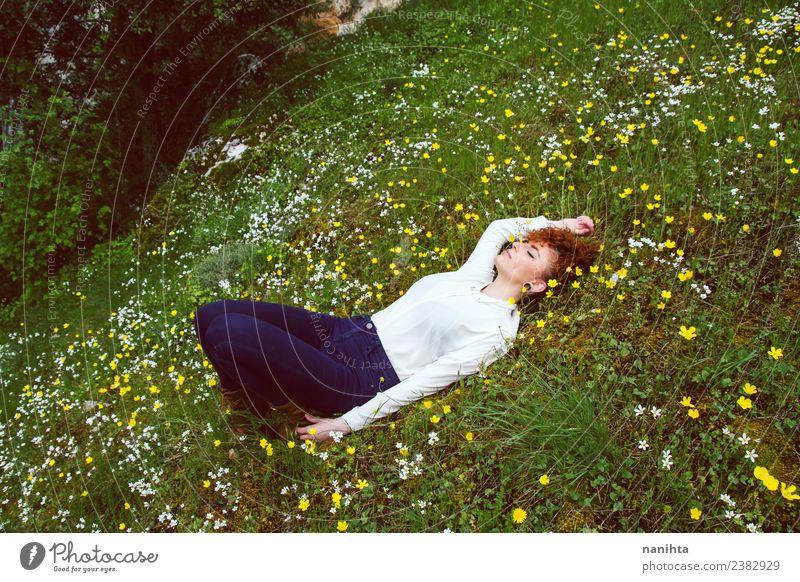 Junge Frau, die sich auf einem Blumenfeld ausruht. Lifestyle Freude Gesundheit Wellness harmonisch Sinnesorgane Erholung ruhig Meditation