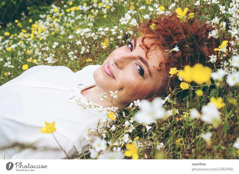 Junge Frau, die sich auf einem Blumenfeld ausruht. Lifestyle Stil Freude Wellness Wohlgefühl Sinnesorgane Erholung Mensch feminin Jugendliche Erwachsene 1
