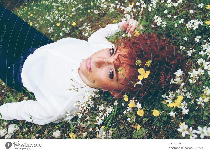 Junge Frau, die sich auf einem Blumenfeld ausruht. Lifestyle elegant Stil Haare & Frisuren Haut Gesicht Gesundheit Wellness Erholung ruhig Duft