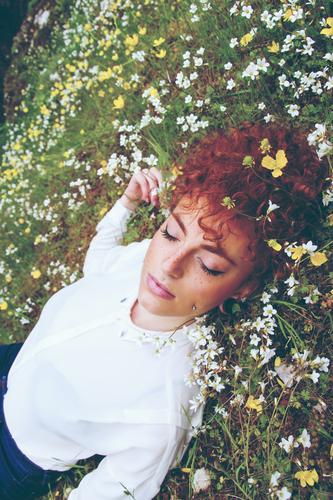 Junge rothaarige Frau, die in einem Blumenfeld schläft. Lifestyle elegant schön Haare & Frisuren Haut Gesicht Gesundheit Wellness harmonisch Wohlgefühl