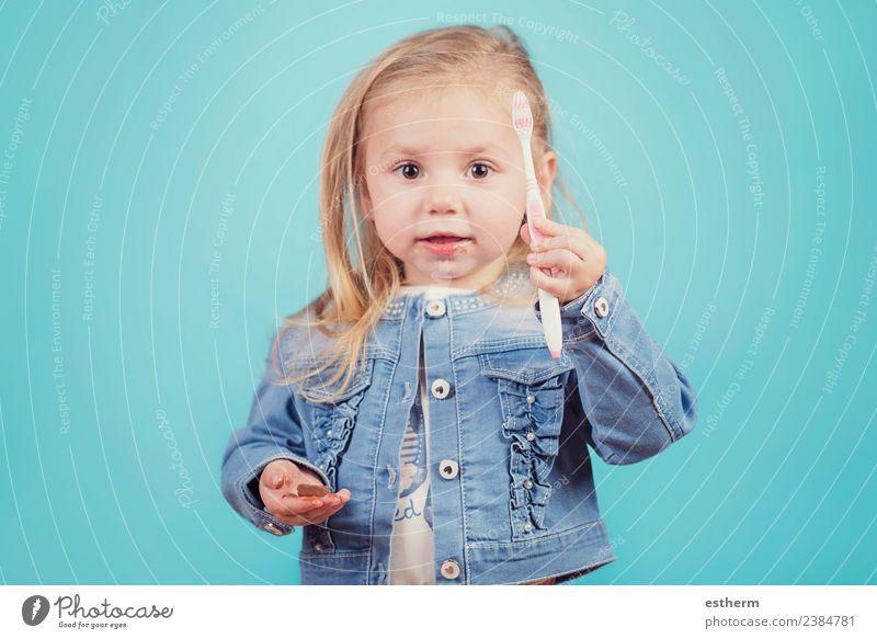kleines Mädchen mit Zahnbürste auf blauem Hintergrund Freude Körperpflege Mensch feminin Baby Kindheit 1 3-8 Jahre festhalten Fitness Lächeln Reinigen