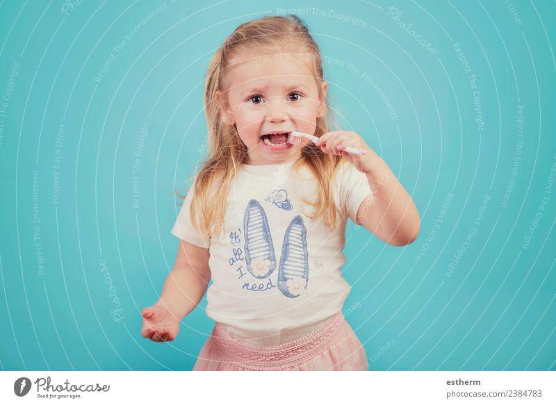 kleines Mädchen mit Zahnbürste auf blauem Hintergrund Lifestyle Freude Körperpflege Gesundheitswesen Mensch feminin Baby Kindheit 1 3-8 Jahre festhalten Fitness