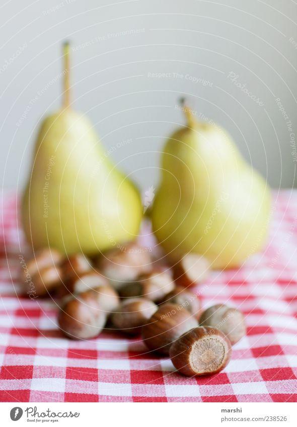 Haselnuss und Birne Lebensmittel Frucht Ernährung braun rot Nuss kariert Stillleben Unschärfe arrangiert Farbfoto Innenaufnahme Tischwäsche