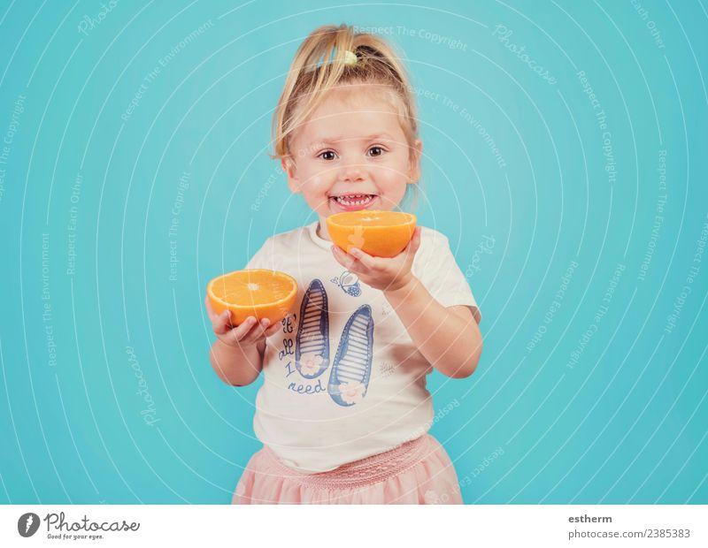 lächelndes Baby mit einer Orange auf blauem Hintergrund Lebensmittel Frucht Ernährung Essen Mittagessen Freude Gesunde Ernährung Mensch feminin Mädchen Kindheit